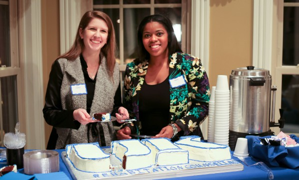 Students serve cake at Rehabilitation Counseling's 50th Celebration