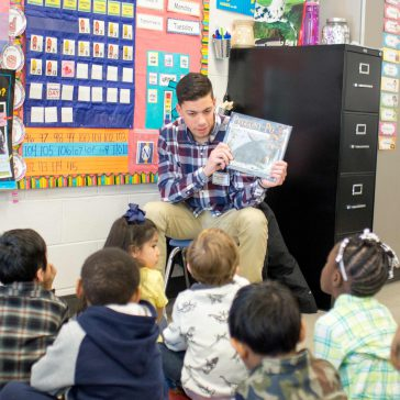 stock photo of male teacher reading to students