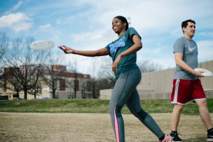 photo of woman playing frisbee