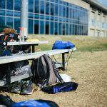 photo of fitness gear and backpacks and books on bleachers