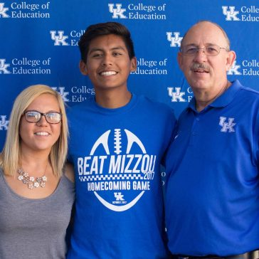 two students and a father at family weekend
