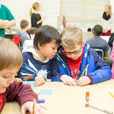 children and teachers collaborating in elementary classroom