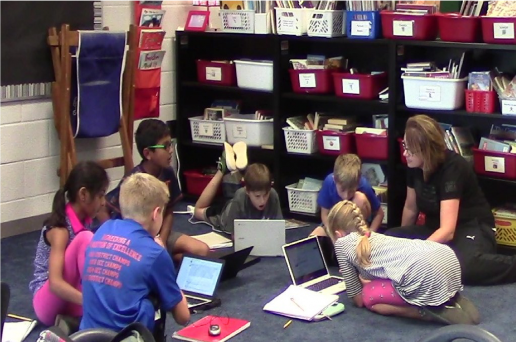 Fourth grade students using laptop computers in a classroom.