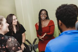 photo of professor Candice Hargons sitting and talking with research students she mentors