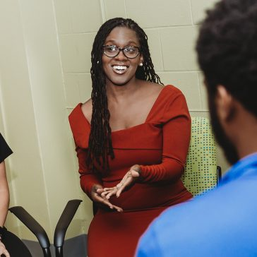 photo of professor Candice Hargons sitting and talking with students at the University of Kentucky College of Education