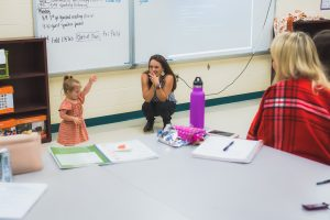 photo of mother watching her daughter , who has Down syndrome, interacting with college students