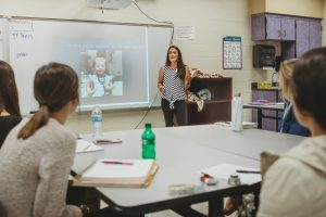 Mother and middle level educator Laura Yost speaks to an audience of college students in an elementary school classroom