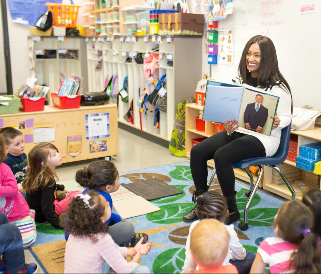 Student teacher holding a book and reading to young children in a classroom.