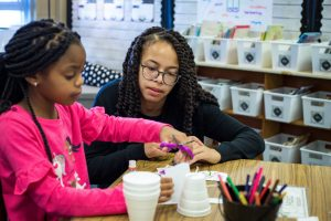 Photo of student teacher Jhana French working with a student at a table