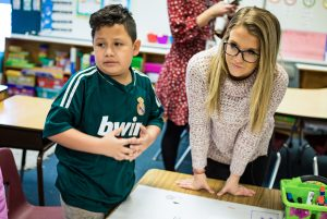 A student teacher working with a student at a table