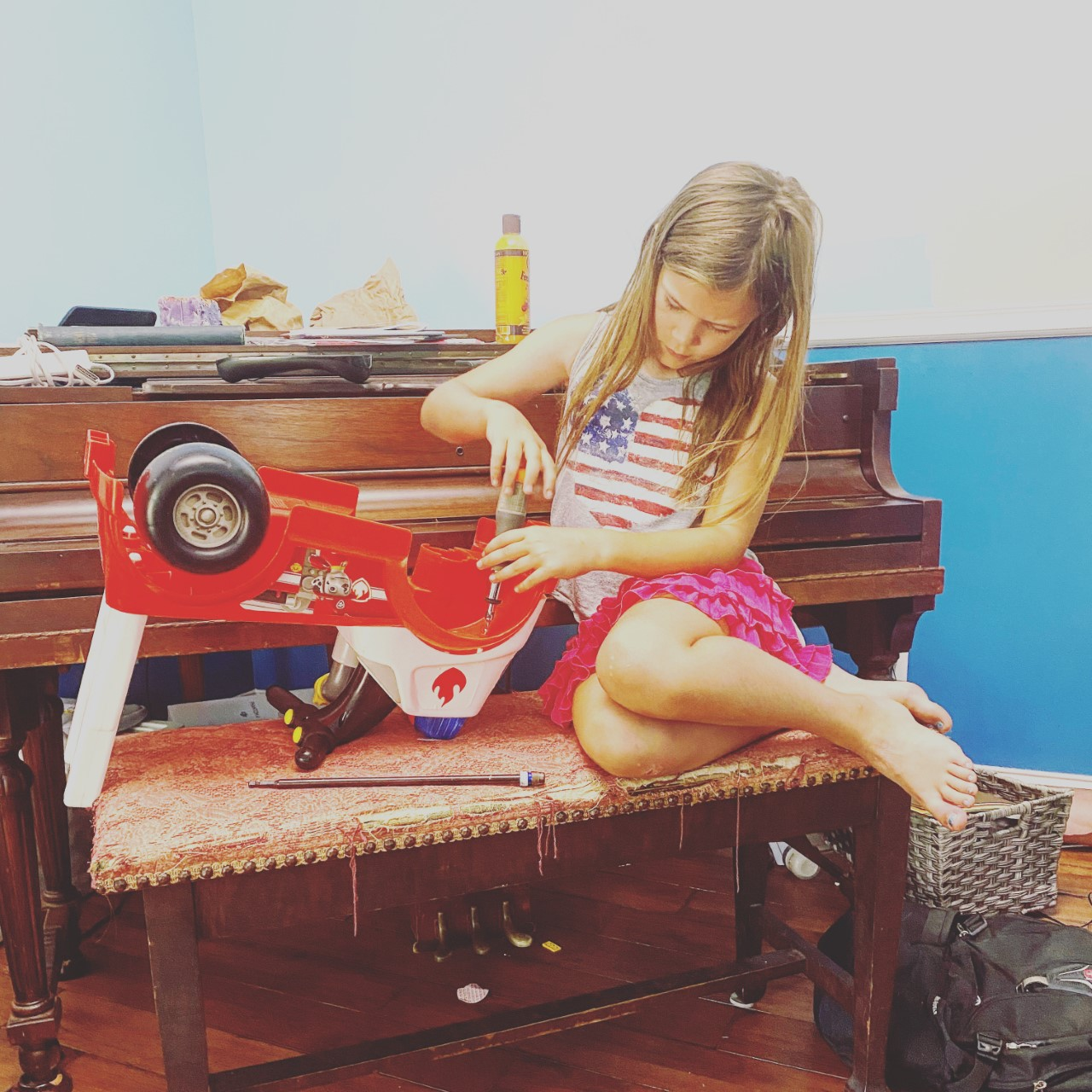 photo of girl using a screwdriver on a toy truck